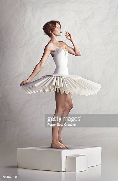 Young woman in white paper craft ballet dress
