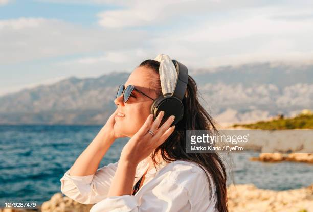 young woman in white shirt listening to music on headphones. beach, summer, golden hour. - golden hour stock pictures, royalty-free photos & images