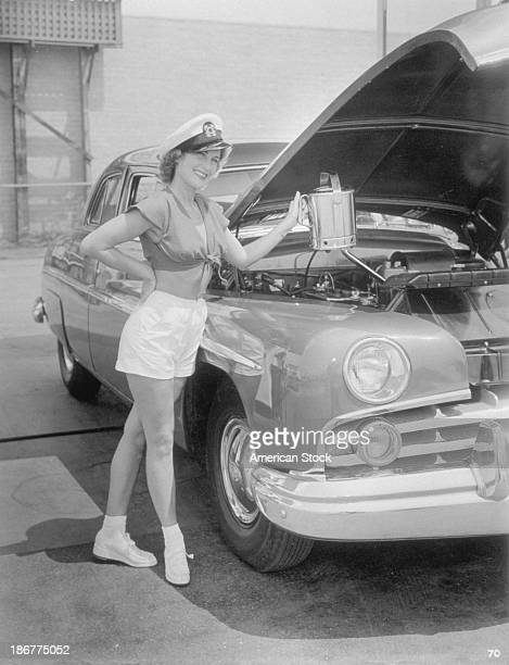 Young woman in white shorts and sailors hat standing at a car with hood up about to add water to car April 12 1950