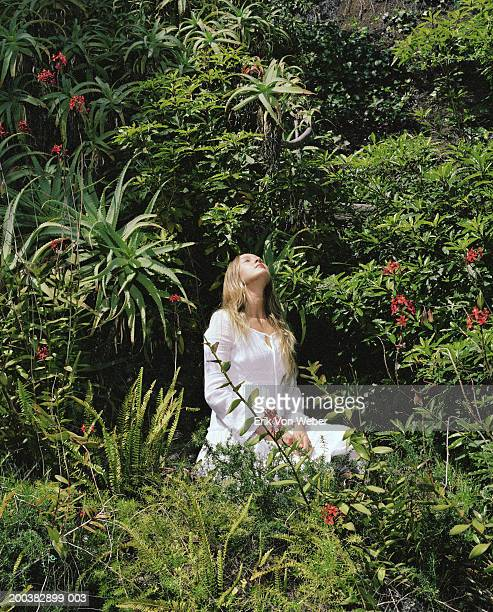 young woman in white sitting in garden - 頭をそらす ストックフォトと画像