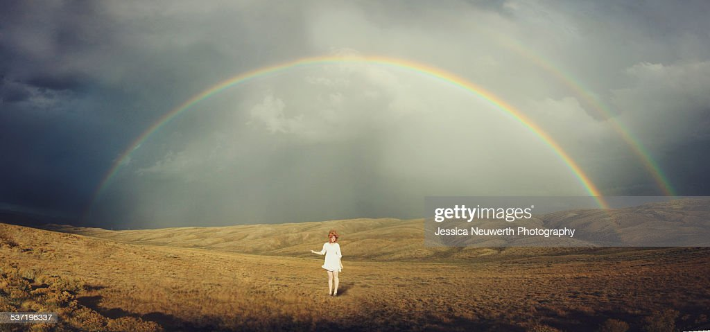 Young woman in white standing below double rainbow : Stock Photo