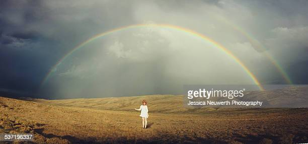 Young woman in white standing below double rainbow