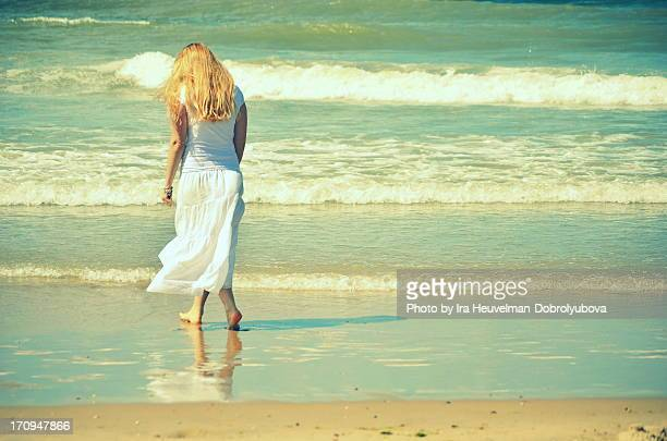 young woman in white walking away on the beach - donne bionde scalze foto e immagini stock