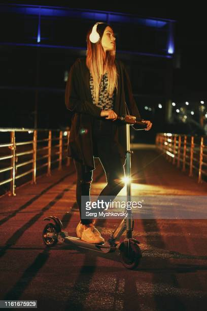 young woman in white wireless headphones riding an electric push scooter through the night streets. - myshkovsky stock photos and pictures