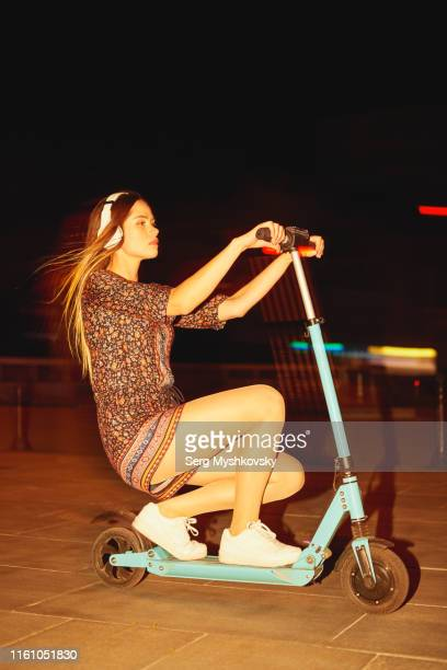 young woman in white wireless headphones riding an electric scooter through the night streets. - myshkovsky stock photos and pictures