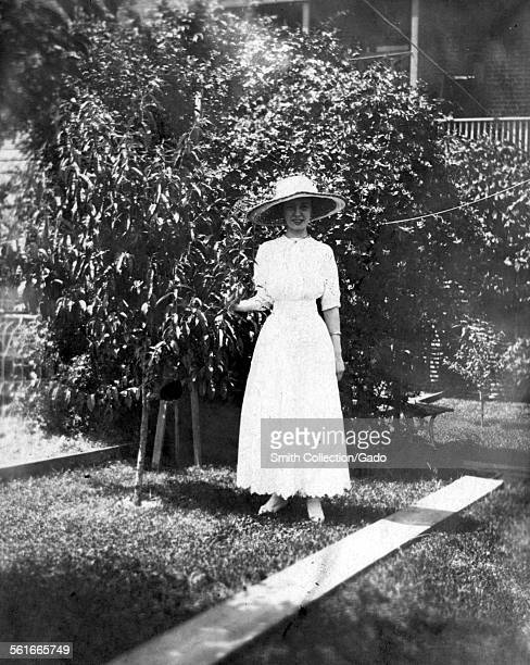 Young woman in wide brimmed hat and dress standing with a large bush in the front yard of a suburban home York Pennsylvania 1943