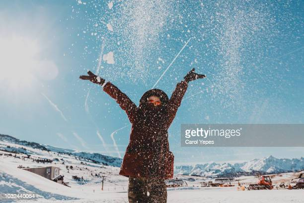 young woman in winter clothes playing with snow - female skier stock pictures, royalty-free photos & images