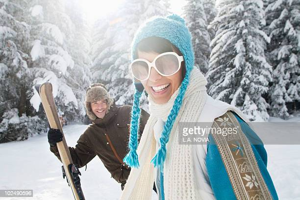 young woman in winter clothes smiling at camera, man holding skis in background - courchevel stock pictures, royalty-free photos & images