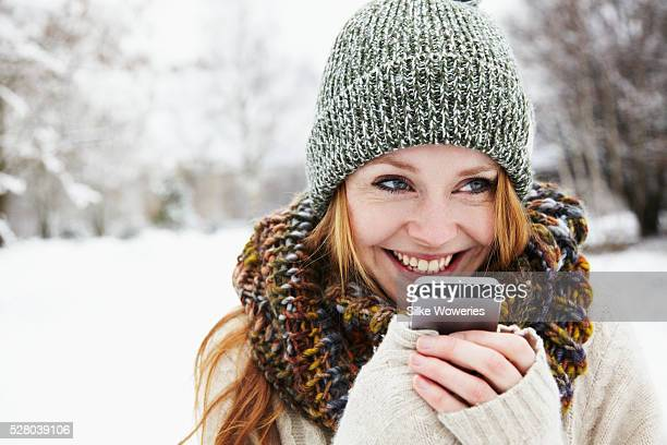 Young woman in winter clothing using phone