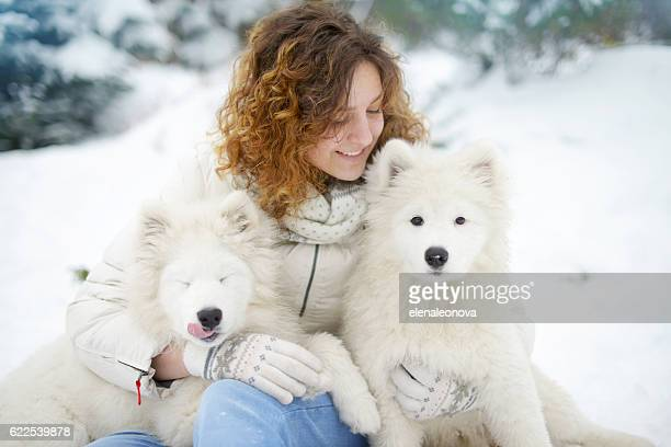 young woman in winter park with white dogs