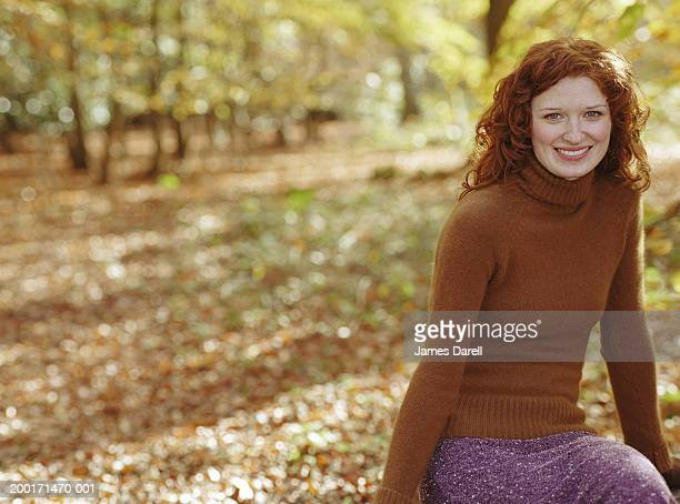 Young woman in woodlands, smiling, portrait