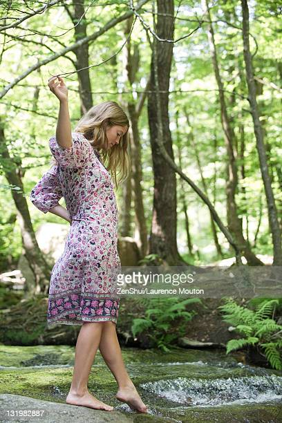 Young woman in woods, dipping toes in stream
