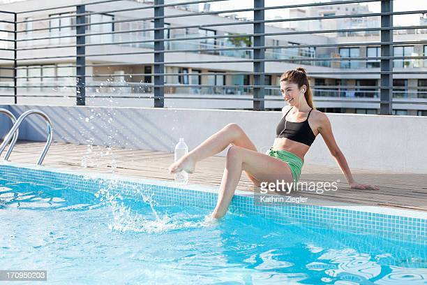 young woman in workout clothes, feet in the pool