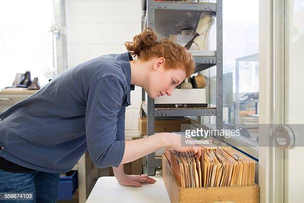 Young woman in workshop looking at card index