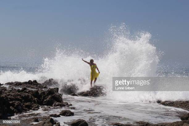 young woman in yellow dress faces the waves approaching - brandung stock-fotos und bilder