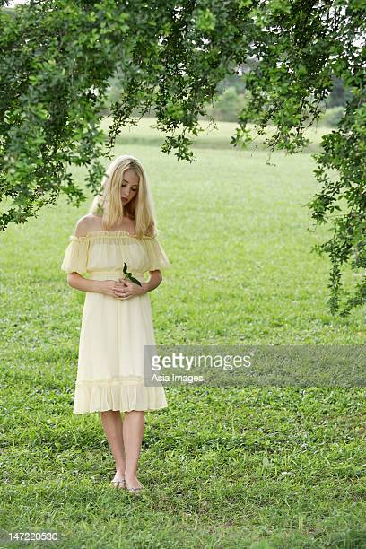 Young woman in yellow dress in green field