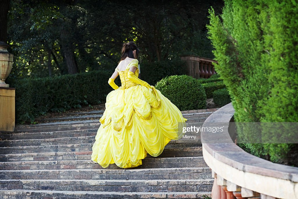 Young Woman in Yellow Dress Running Up Stairs : Stock Photo