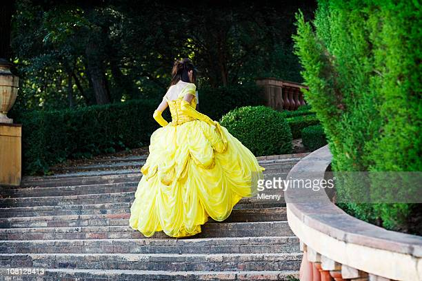 young woman in yellow dress running up stairs - snow white stock photos and pictures