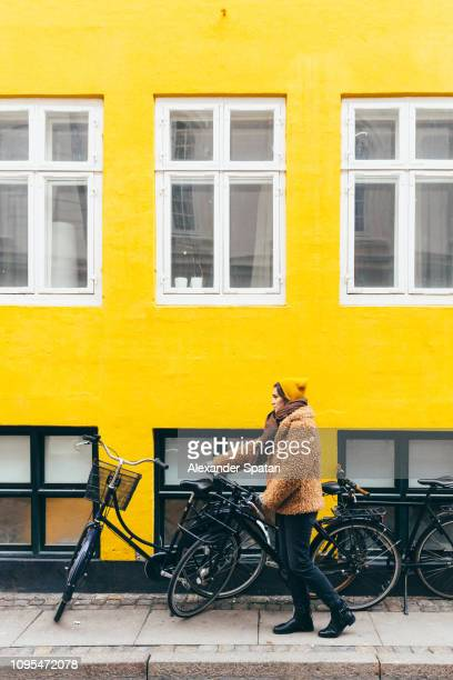 young woman in yellow hat and fake fur holding bike against yellow wall - copenhague photos et images de collection