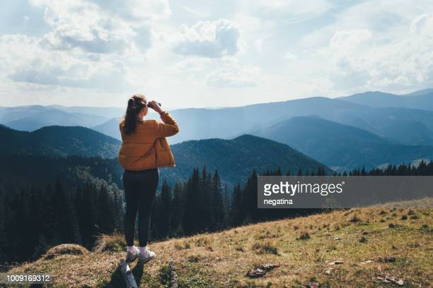 young woman in yellow jacket looks with binoculars on the mountain standing back to the camera - ukraine landscape stock pictures, royalty-free photos & images