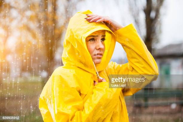 Young woman in yellow raincoat on the rain