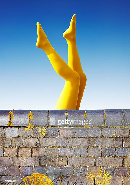 young woman in yellow tights with legs in the air. - appearance stock pictures, royalty-free photos & images