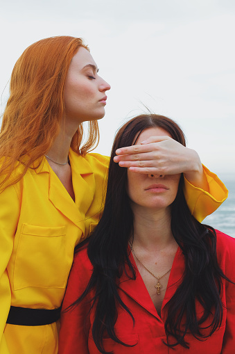 Young woman in yellow with closed eyes closes the eyes of a young woman in red - gettyimageskorea