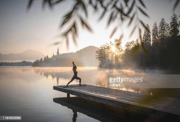 jeune femme dans la position élevée de poumon de yoga à l'aube dans bled - bien être photos et images de collection