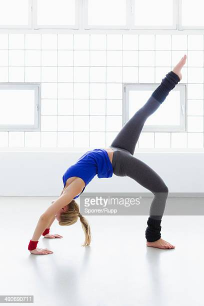 young woman in yoga position - レッグウォーマー ストックフォトと画像