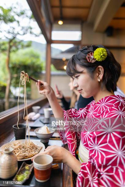 young woman in yukata eating soba for lunch - soba stock pictures, royalty-free photos & images
