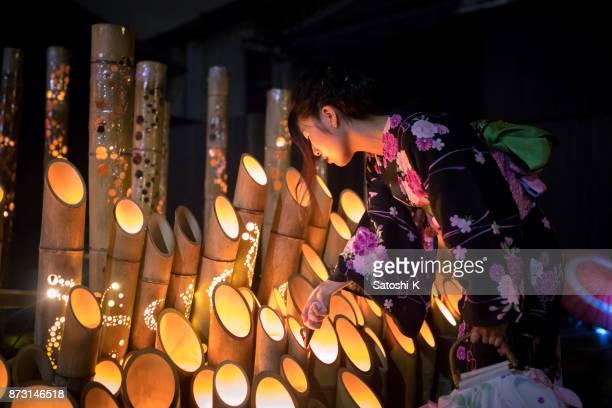 竹キャンドル ライトに近づいて浴衣の若い女性 - 工芸品 ストックフォトと画像