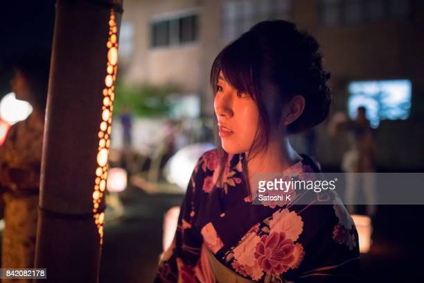 竹の棒でキャンドル ライトを見て浴衣の若い女性 - ボン ストックフォトと画像