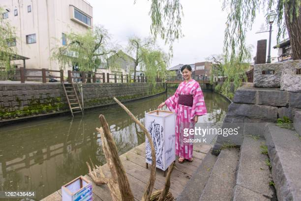 young woman in yukata visiting japanese summer event - obi sash stock pictures, royalty-free photos & images