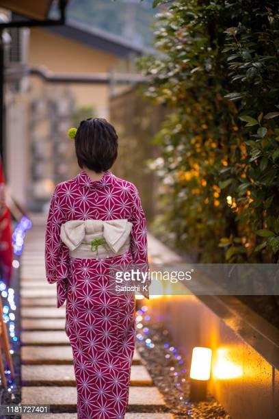 夕暮しの時間に狭い歩道を歩く浴衣の若い女性 - 帯 ストックフォトと画像