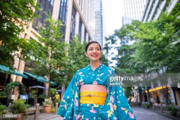 young woman in yukata walking on city street on weekend - obi sash stock pictures, royalty-free photos & images