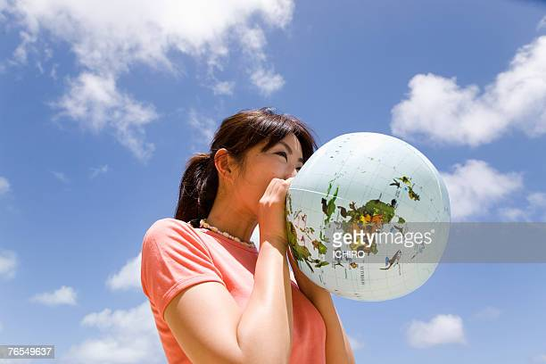 Young woman inflating balloon in form of Earth,outdoors,low angle view