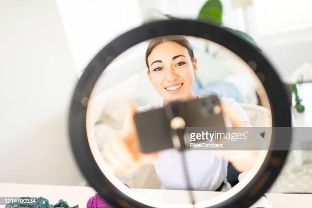 jeune influenceur de femme installant le téléphone intelligent dans la lumière d'anneau - influenceur photos et images de collection