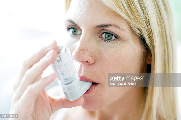 Young woman inhaling asthma inhaler, close-up