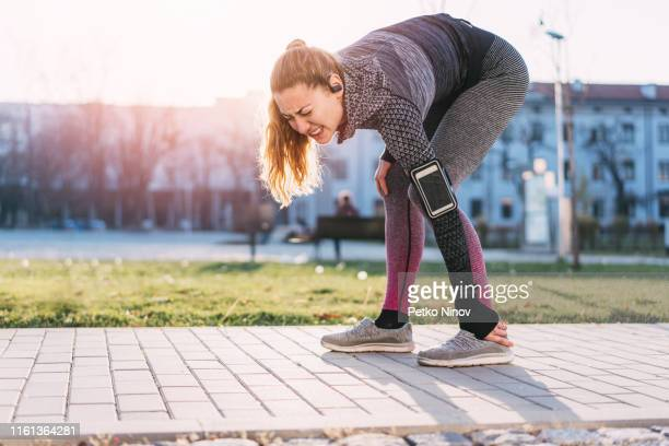 young woman injuring her left ankle - human limb stock pictures, royalty-free photos & images