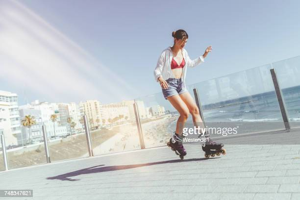 Young woman inline skating on boardwalk at the coast