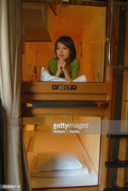 Young Woman inside Capsule Hotel Room