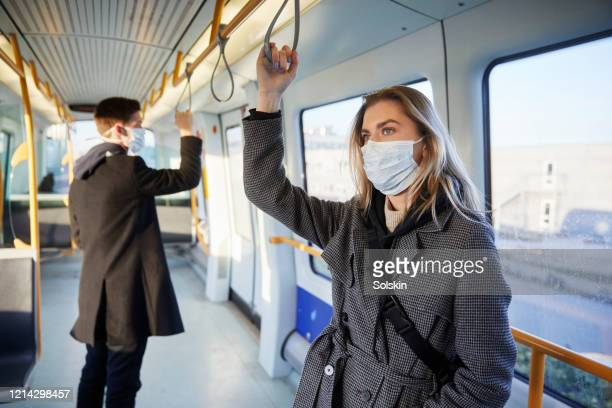 young woman inside train, wearing a virus protective face mask - distancia social fotografías e imágenes de stock