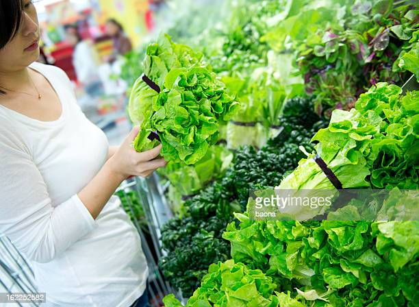 Young woman inspecting the lettuce
