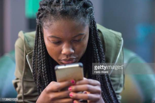 young woman intently reading cell phone - news event stock pictures, royalty-free photos & images