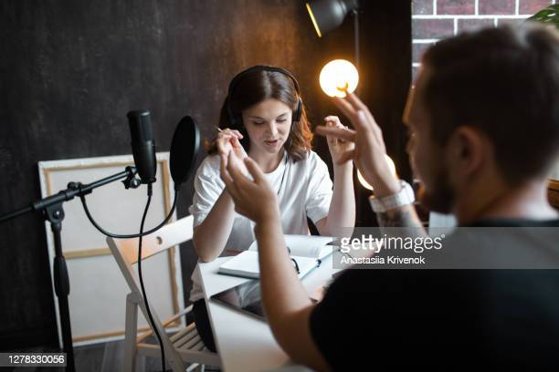 young woman interviewing a guest in studio for podcast. - journalist stock pictures, royalty-free photos & images