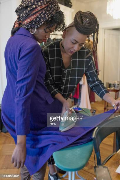 A young woman ironing a coat
