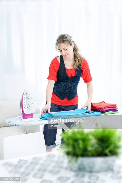 young woman ironing and folding clothes - izusek stock pictures, royalty-free photos & images