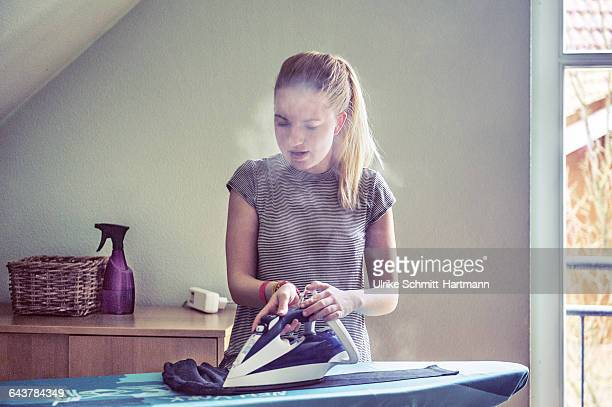 Young woman, ironing with a steam iron