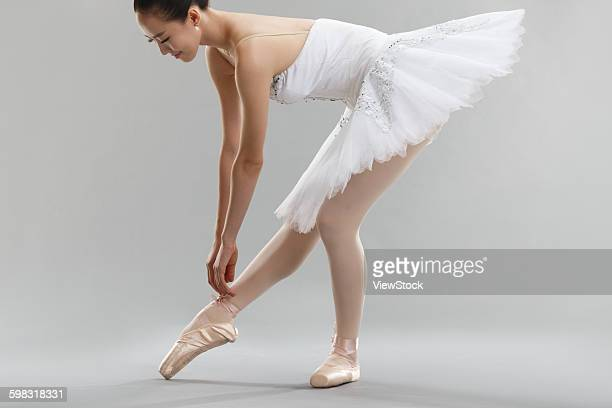 Young woman is a ballet shoe lace