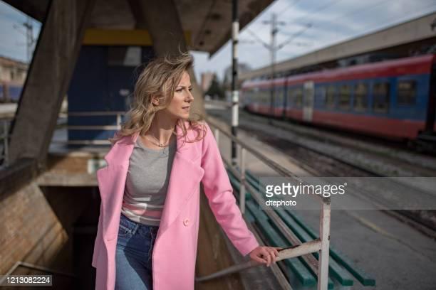 年輕女子獨自在火車站 - 女裝 個照片及圖片檔